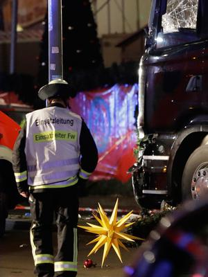 A firefighter walks past a star after a truck ran into crowded Christmas market in Berlin, Germany, Monday, Dec. 19, 2016, killing several people. (AP Photo/Michael Sohn)