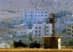 In this image shot with an extreme telephoto lens and through haze from the outskirts of Suruc at the Turkey-Syria border, Turkish forces armoured vehicles patrol the border as a black banner with white writing is seen atop of a building at the eastern side of the town of Kobani, Syria, where fighting had ben intensified between Syrian Kurds and the militants of Islamic State, Monday, Oct. 6, 2014. Kobani, also known as Ayn Arab and its surrounding areas have been under attack since mid-September, with militants capturing dozens of nearby Kurdish villages. The flag is indicating that the jihadists may have regrouped and broken through the Kurdish lines.(AP Photo/Lefteris Pitarakis)