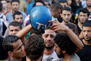 Palestinian freelance photographer Motaz Al Salhy, center, accompanied by colleagues, cries as he holds the bloodied helmet of his friend, freelance cameraman Rami Rayan, who was killed while working, in an Israeli strike in Shijaiyah neighborhood outside the morgue of Gaza City's Shifa hospital, on Wednesday, July 30, 2014. (AP Photo/Lefteris Pitarakis)