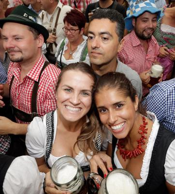 MUNICH, GERMANY - SEPTEMBER 20:  Revellers reach for the first beer mugs at Hofbraeuhaus beer tent during the opening day of the 2014 Oktoberfest on September 20, 2014 in Munich, Germany. The 181st Oktoberfest will be open to the public from September 20 through October 5 and traditionally draws millions of visitors from across the globe to the the world's largest beer festival.  (Photo by Johannes Simon/Getty Images)