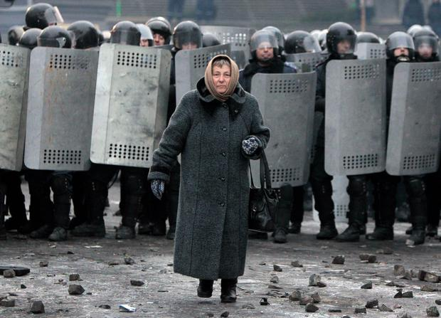 An elderly woman walks from police officers as they block a street during unrest in central Kiev, Ukraine,Tuesday, Jan. 21, 2014. Anti-government protesters have held their ground through a night of violent street clashes in the Ukrainian capital, despite police moving in to dismantle barricades erected in a street leading to government offices. Police attempted to move in on the protest camp early Tuesday, but faced fierce resistance from demonstrators who tossed fire bombs and stones in their direction. (AP Photo/Sergei Chuzavkov)