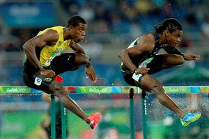 Andrew Riley of Jamaica (L) and Eddie Lovett of Virgin Islands (US) compete during the Men's 110m Hurdles Round 1 - Heat 3. (Photo by Patrick Smith/Getty Images)