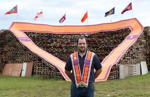 PACEMAKER, BELFAST, 11/7/2020: The sash my father wore! Kyle Branyan, Worshipful Master of LOL 31, Kilmoriarty Bible and Crown Defenders, has his picture taken in front of the giant sash that adorns the Twelfth bonfire at Edgarstown in Portadown, Co Armagh  PICTURE BY STEPHEN DAVISON