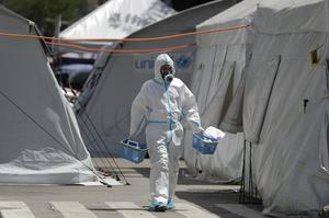 A health worker walks in between tents in a car park that has been converted into an extension of the Gat Andres Bonifacio Memorial Medical Centre in Manila (Aaron Favila/AP)
