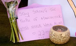 Tributes left outside St Ann's Church in Manchester, the morning after a suicide bomber killed 22 people, including children, as an explosion tore through fans leaving a pop concert, at Manchester Arena.