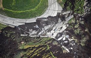 In this aerial photo, the landslide caused by the earthquake disrupts the road in Minamiaso town, Kumamoto prefecture, southern Japan Saturday, April 16, 2016. A powerful earthquake struck southern Japan early Saturday, barely 24 hours after a smaller quake hit the same region.(Kyodo News via AP)