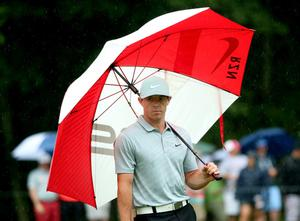 LOUISVILLE, KY - AUGUST 08: Rory McIlroy of Northern Ireland stands under an umbrella on the 15th green during the second round of the 96th PGA Championship at Valhalla Golf Club on August 8, 2014 in Louisville, Kentucky.  (Photo by Andrew Redington/Getty Images)