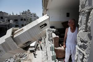 Palestinian Ismail Radwan, 45, inspects the damage to his family apartment caused by a fallen minaret of the Al-Sousi mosque, that was destroyed in an Israel strike, at Shati refugee camp, in the northern Gaza Strip, Wednesday, July 30, 2014.(AP Photo/Lefteris Pitarakis)