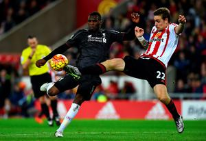 Christian Benteke of Liverpool attempts to shoot at goal under pressure from Sebastian Coates of Sunderland during the Barclays Premier League match between Sunderland and Liverpool at Stadium of Light on December 30, 2015 in Sunderland, England.  (Photo by Stu Forster/Getty Images)