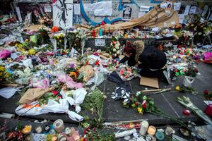 A woman lights a candle amongst tributes laid to victims of the Paris attacks at the foot of the Monument a La Republique in Paris on November 16, 2015.    Islamic State jihadists claimed a series of coordinated attacks by gunmen and suicide bombers in Paris on November 13 that killed at least 129 people in scenes of carnage at a concert hall, restaurants and the national stadium. AFP PHOTO /  LIONEL BONAVENTURELIONEL BONAVENTURE/AFP/Getty Images
