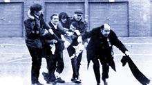The body of Jackie Duddy is carried away, led by the crouched figure of Fr Edward Daly carrying a bloodstained hankerchief, on Bloody Sunday