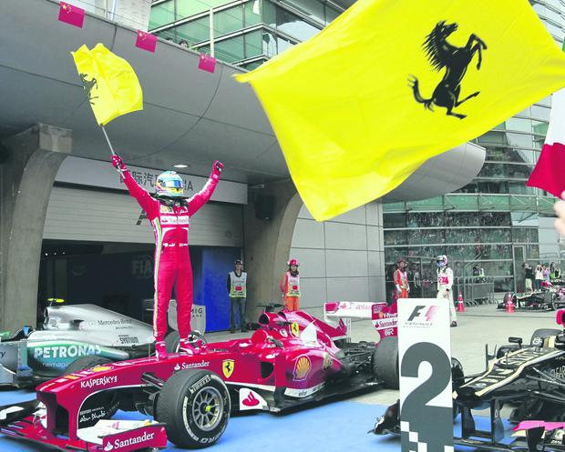 Ferrari driver Fernando Alonso of Spain stands on his car and waves a flag as he celebrates his win at the Chinese Formula One Grand Prix in Shanghai, China, Sunday, April 14, 2013. (AP Photo/Eugene Hoshiko)