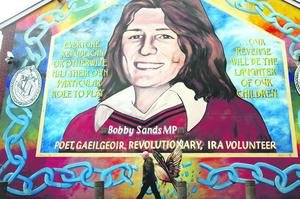 A man walks past the Bobby Sands mural, in the Falls road area of Belfast