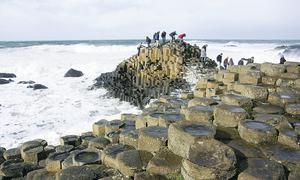 Visitors walk along the basalt rocks at the Giants Causeway in Northern Ireland