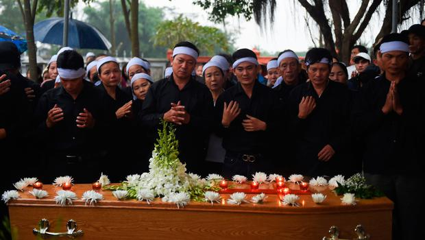 Family members of Hoang Van Tiep pray over his coffin at the cemetery