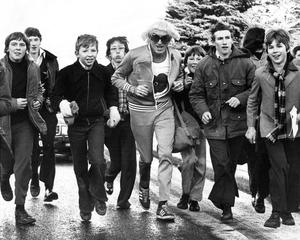 Double life: Jimmy Savile taking part with schoolboys in a sponsored walk on the Ravenhill Road in Belfast