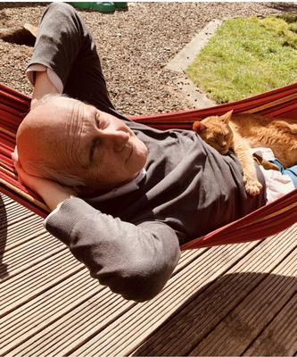 Cat nap: Alex Kane relaxes in a hammock with the family cat on his lap