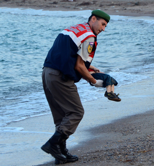 A Turkish police officer carries a migrant child's dead body off the shores in Bodrum, southern Turkey