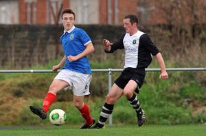 Passing up: Linfield Swifts' Karl Devine attempts to find a team-mate as Dromara's Mark Drake looks on