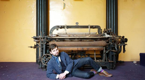 Belfast-based clothing designer Chris Tydall in front of a long disused loom