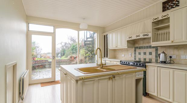 The kitchen is traditional with a glass front leading outside