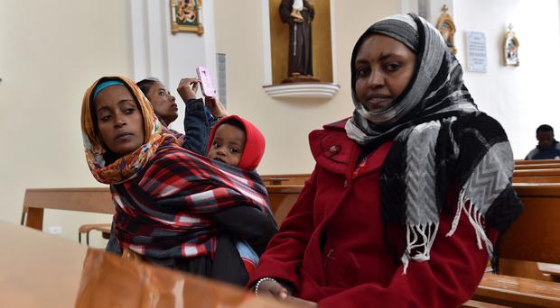 Escaping terror: migrants fleeing attacks by Isis in Libya sit in a Catholic church in Lampedusa, Italy