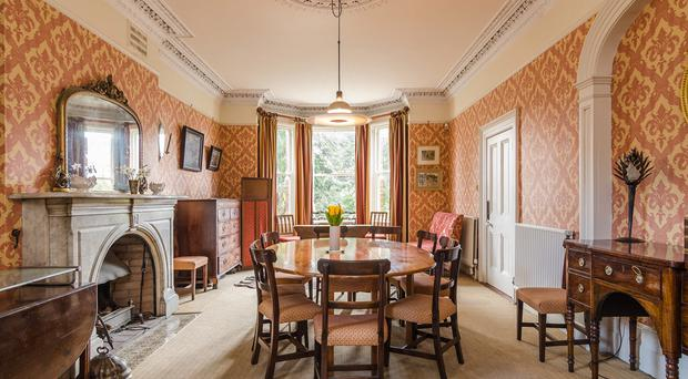 The dining room boasts a bay window and marble fireplace