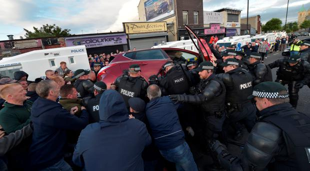 Police attempt to free a young girl trapped underneath a car at the Ardoyne flashpoint