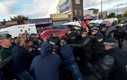 Sorry sight: police attempt to free a young girl trapped underneath a car at the Ardoyne flashpoint