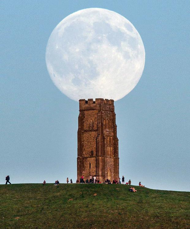 This is the awe-inspiring sight of a full moon rising over people gathered on Glastonbury Tor in Somerset ahead of this week's so-called 'Blue Moon'