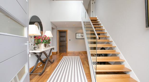 The hallway has a solid wood floor with glass banister