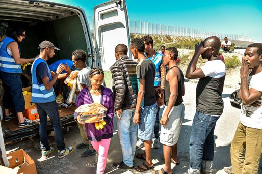 Helping hand: migrants queue for food being handed out by a humanitarian organisation
