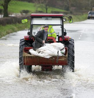 A farmer moves livestock threatened by rising floodwaters at Hilltown, near Newry, on Wednesday as Storm Frank continued to wreak havoc across Northern Ireland