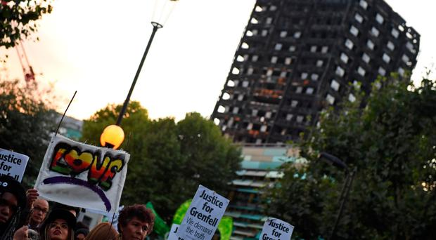 Inquiry time: overlooked by the shell of the tower, people take part in a silent march in memory of the victims of the Grenfell fire