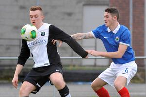 Arm's length: Linfield Swifts' Jack Smith puts Gerard Rooney of Dromara under pressure