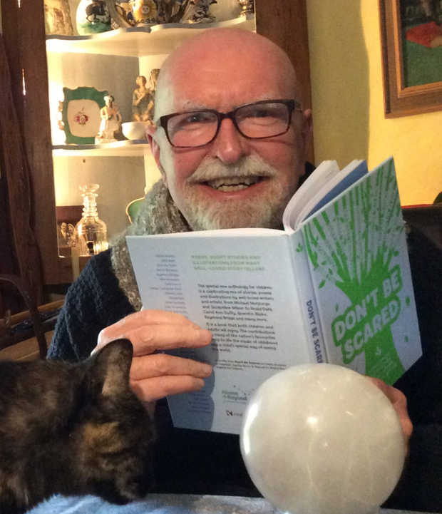 Author Herbie Brennan relaxes at home with a book and his cat