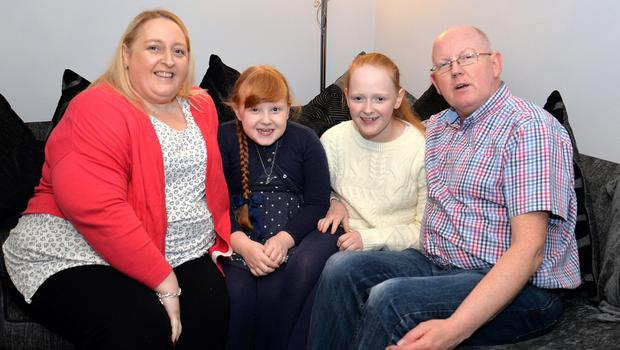 Tanya and Norman Phillips with daughters Ruby (left) and Hollie. The sisters will switch on the Christmas lights at the Northern Ireland Hospice in memory