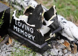 An urn smashed by vandals in a graveyard