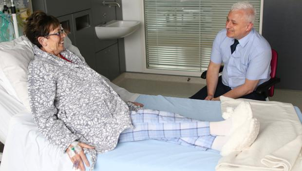 Chaplain Don Gamble talking to a patient at the hospital