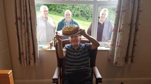 Larry Fay celebrating his 91st birthday with his sons at his window