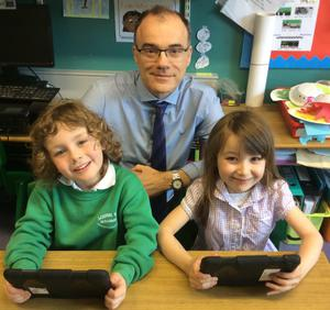 Early learning: Primary School pupils Dexter and Maya use their iPads with the school principal Michael McKnight