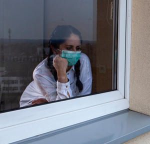 Time rich: a woman in quarantine stares out window