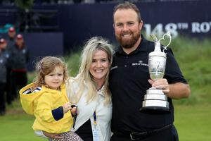 Shane Lowry holds the Claret Jug with wife Wendy and daughter Iris