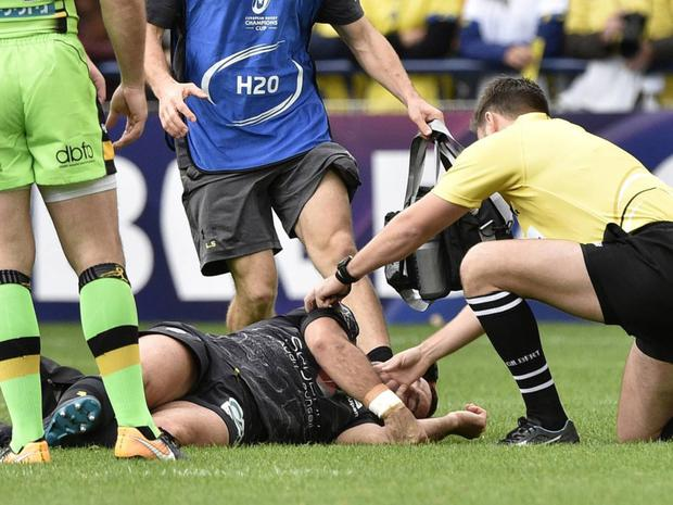 High risks: a rugby player is treated for a head injury