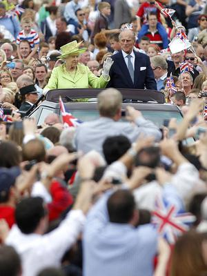 Queen Elizabeth II and the Duke of Edinburgh wave to the crowds in the grounds of Stormont in Belfast