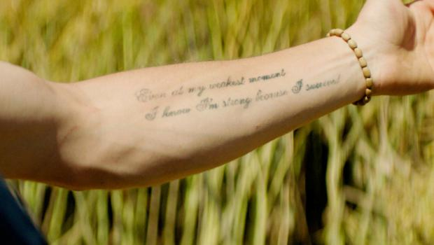 His distinctive arm tattoo which reads: 'Even in my weakest moments I know I'm strong because I survived'