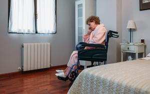 Tough times: a woman sitting on her own in a care home