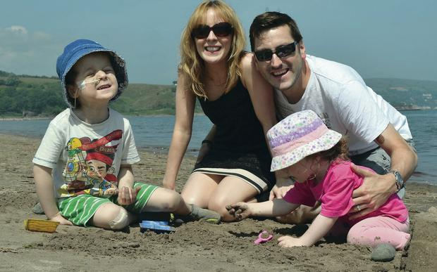 Short break: Oscar Knox enjoying a day at the seaside with mum Leona, dad Stephen and little sister Isobella