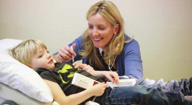 Dr Lisa Neligan injects her son David (four)