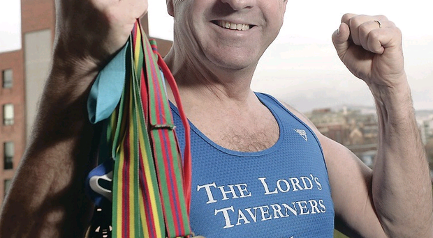 Running man: Leo shows off his medal collection from the charity races he has taken part in